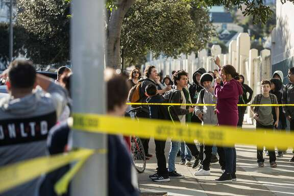 James Lick Middle School students crowd behind caution tape after at least ten students were sickened after ingesting an unknown substance Tuesday, Feb. 13, 2018 in San Francisco, Calif.
