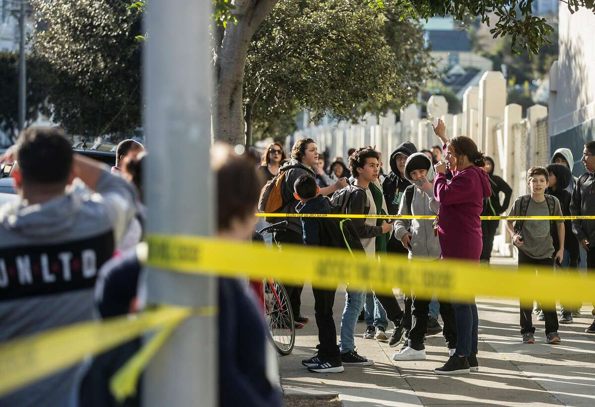 James Lick Middle School students crowd behind caution tape after at least ten students were sickened after ingesting cannabis.