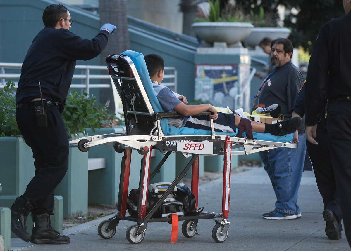 A boy is taken out by rescue officials on a stretcher after at least ten students were sickened at James Lick Middle School.