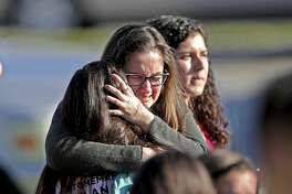 Students released from a lockdown embrace following following a shooting at Marjory Stoneman Douglas High School in Parkland, Fla., Wednesday, Feb. 14, 2018.