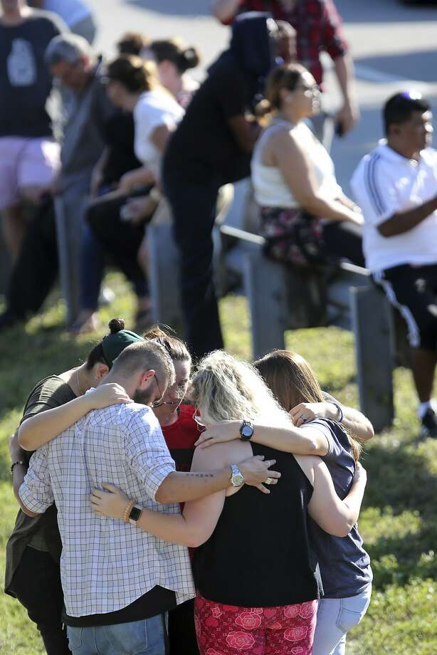 People gather outside the campus of Marjory Stoneman Douglas High School in Parkland, Fla., after a shooting that left 17 dead. Photo: Amy Beth Bennett, Associated Press