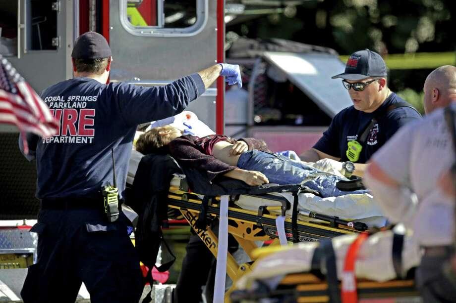 Medical personnel tend to a victim following a shooting at Marjory Stoneman Douglas High School in Parkland, Fla., on Wednesday, Feb. 14, 2018. (John McCall/South Florida Sun-Sentinel via AP) Photo: John McCall, MBO / Associated Press / South Florida Sun-Sentinel