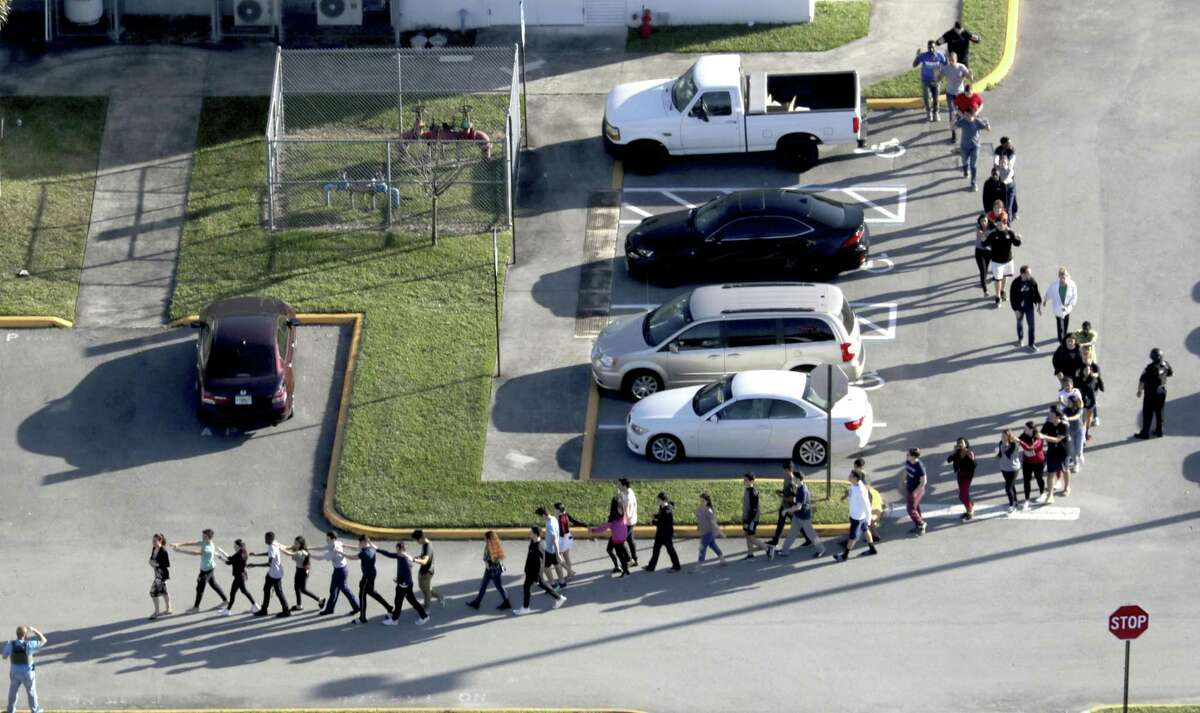 Students are evacuated by police from Marjorie Stoneman Douglas High School in Parkland, Fla., on Wednesday, Feb. 14, 2018, after a shooter opened fire on the campus. (Mike Stocker/South Florida Sun-Sentinel via AP)