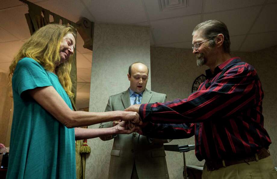 Amy Graham, left, and James Spicer, right, hold hands as chaplain Spencer Littlejohn, center, officiates their wedding at Champion Forest Baptist Church Wednesday, Feb. 14, 2018, in Houston. Spicer and Graham, each, have spent about 15 years living homeless. They met 10 years ago and camped together in the northwest wooded area of Houston.  ( Godofredo A. Vasquez / Houston Chronicle ) Photo: Godofredo A. Vasquez, Houston Chronicle / Godofredo A. Vasquez