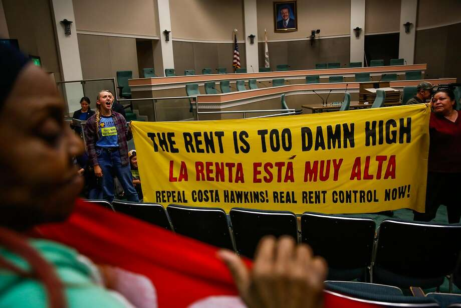 Sara Linckfrenz, second from left, and Marisela Garcia Perez, right, hold up a sign in protest after a bill to repeal the Costa Hawkins Rental Housing Act did not pass at the State Capital in Sacramento. Photo: Gabrielle Lurie, The Chronicle