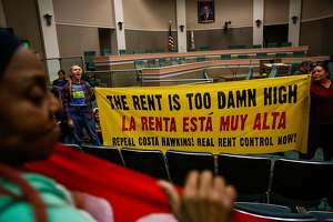 Sara Linckfrenz ( second from left) and Marisela Garcia Perez (right) hold up a sign in protest after a bill to repeal the Costa Hawkins Rental Housing Act did not pass at the State Capital in Sacramento, Calif., on Thursday, Jan. 11, 2018.