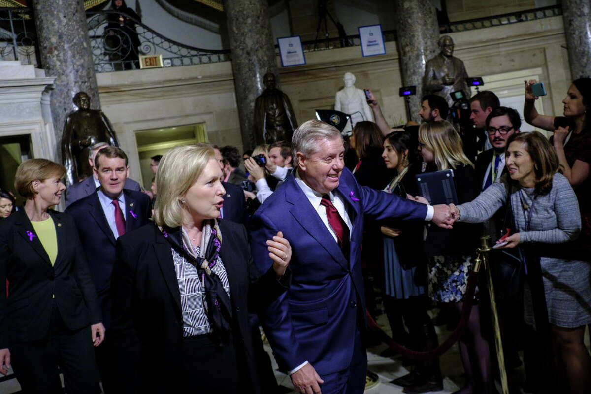 WASHINGTON, DC - JANUARY 30: U.S. Sens. Kirsten Gillibrand (D-NY) and Lindsey Graham (R-SC) make their way to the House of Representatives chamber for President Donald Trump's first State of the Union Address before a joint session of Congress on January 30, 2018 in Washington, DC. (Photo by Pete Marovich/Getty Images)
