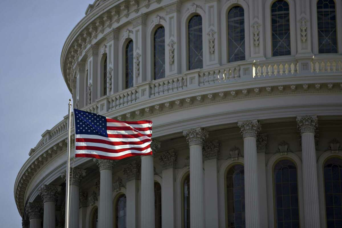 The American flag flies next to the dome of the U.S. Capitol building on Jan. 15, 2017.( Bloomberg photo by Andrew Harrer)