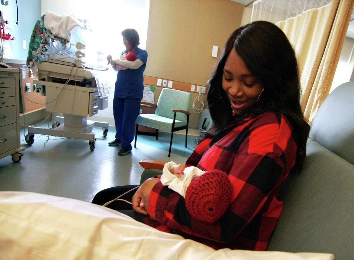 Natasha Parker holds her son Jesaiah at the new Allison Family Neonatal ICU at Bridgeport Hospital campus of Yale New Haven Children's Hospital in Bridgeport, Conn., on Wednesday Feb. 14, 2018. In back is RN Juliet Rosario who is bringing over Jesaiah's twin sister Jenesis. They were born on Jan. 25th at 10 weeks premature.