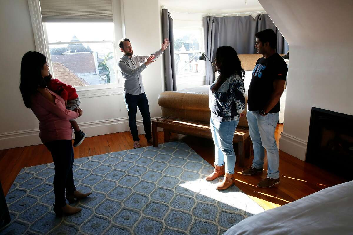Ryan Booth, (left center) with his guests, (l to r) Vaishnavi Tanneru and her son Viaan, 2, Meher and Sudhir Kaveti, as he welcomes them to his home and the bedroom he renting to them through Airbnb, in San Francisco, Calif., on Monday Feb. 5, 2018. Booth is able to afford his San Francisco flat by renting out his bedroom down the hall through Airbnb.