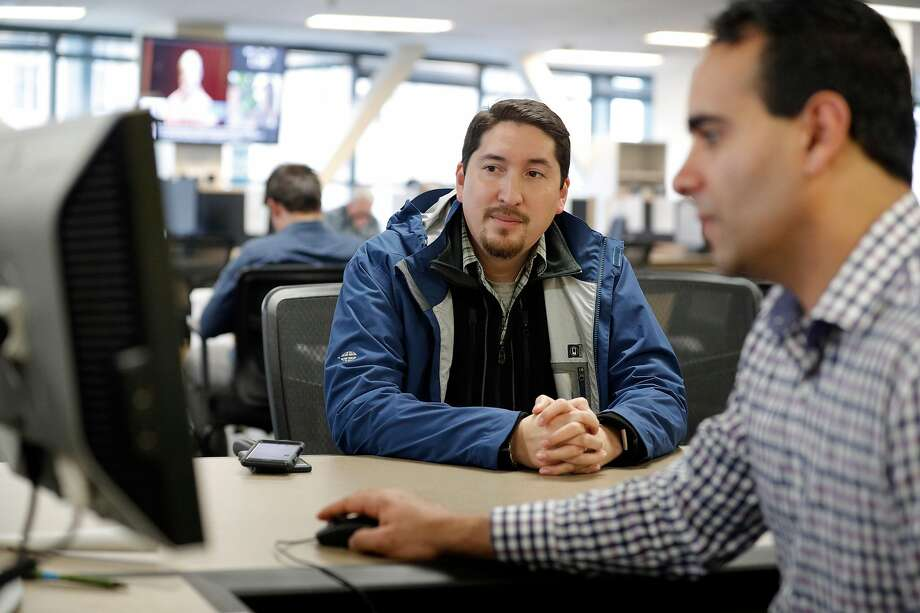 Gustav Choto (left) talks with Omar Masry, a senior analyst at the Office of Short-Term Rentals in San Francisco, days before the January deadline for Airbnb hosts to register with the city. Photo: Carlos Avila Gonzalez, The Chronicle