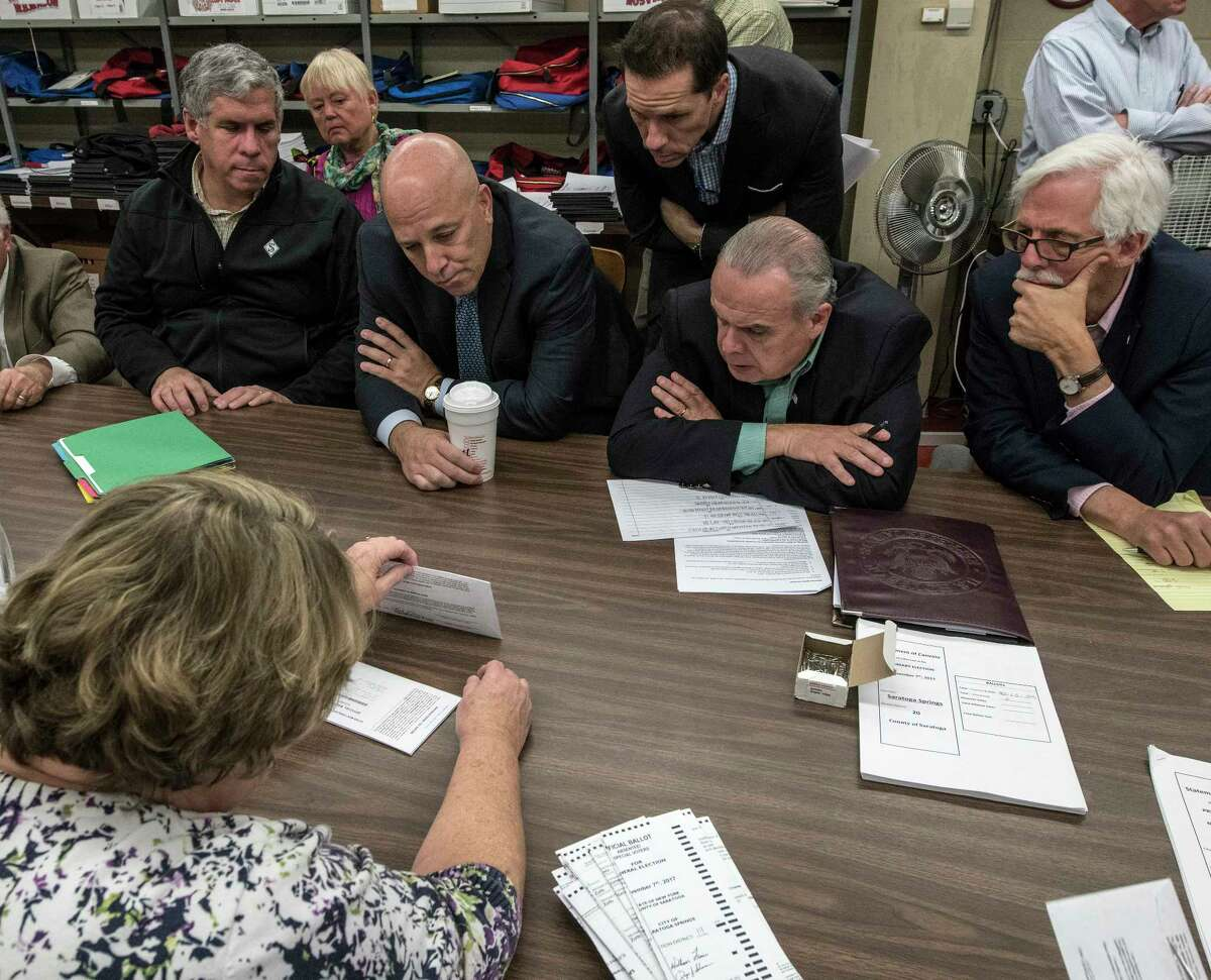 Representatives huddle up over the recount of absentee ballots in the City of Saratoga election as they look closely at the City Charter vote and the race for the Public Safety Commissioner Tuesday Nov. 14, 2017 at the Saratoga County Board of Elections offices in Ballston Spa, N.Y. (Skip Dickstein/ Times Union)