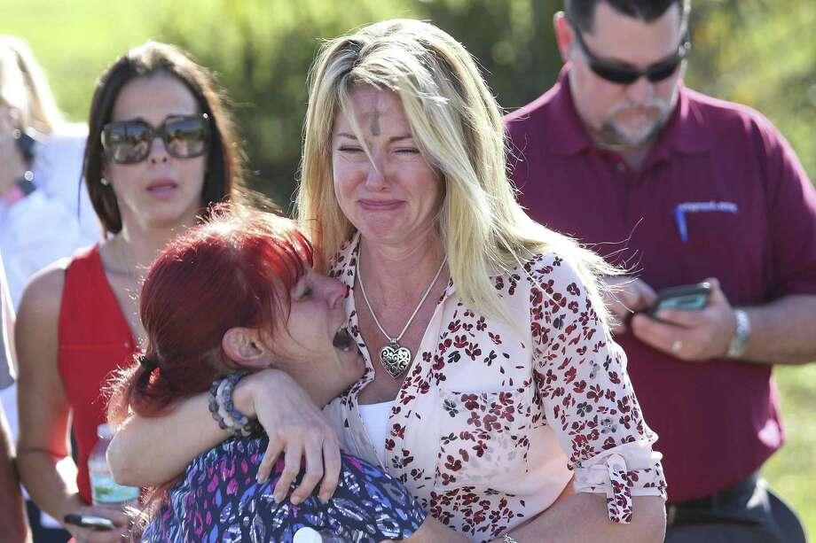 Dos mujeres lloran tras el reporte de un tiroteo en la Escuela Secundaria Marjory Stoneman Douglas de Parkland, Florida, el miércoles 14 de febrero de 2018. Photo: Joel Auerbach /Associated Press / ONLINE_YES