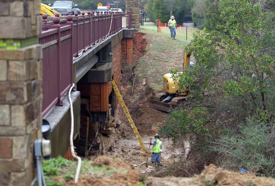 Work continues on repairing stabilizer material beneath a bridge on Woodforest Parkway that had been eroded, Wednesday, Feb. 14, 2018, in Montgomery. Despite the erosion, engineers indicated there was no structural damage to the bridge. Photo: Jason Fochtman, Staff Photographer / © 2018 Houston Chronicle