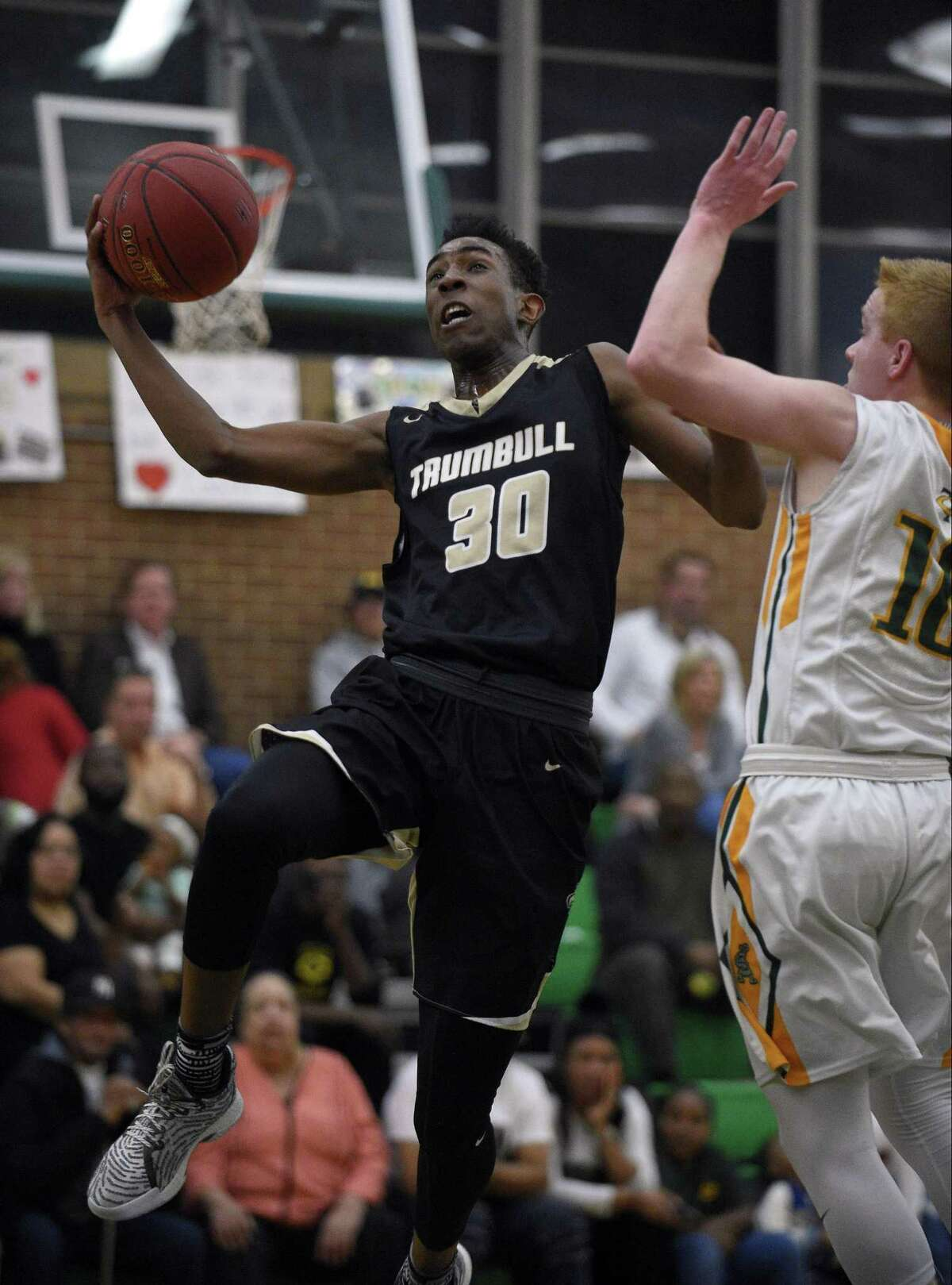 Trumbull Timmond Williams (30) puts up a shot against Trinty Catholic's Jack Soucy (10) during an FCIAC Boys Basketball game at Trinity Catholic High School on Wednesday, Feb. 14, 2018 in Stamford, Connecticut.