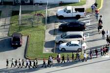 Students are evacuated by police from Marjory Stoneman Douglas High School in Parkland, Fla., on Wednesday after a shooter opened fire on the campus. The suspected gunman was taken into custody by authorities, but not before 17 people were reported killed.