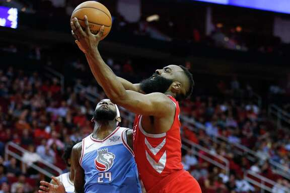 Rockets guard James Harden, who fininshed just short of a triple-double Wednesday, is fouled on the way to the bucket by the Kings' JaKarr Sampson (29).
