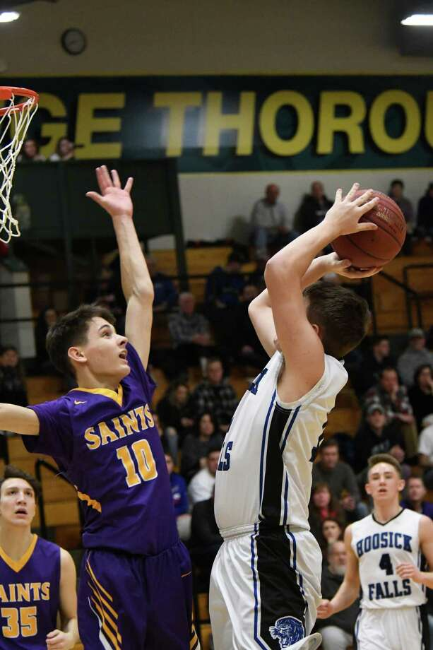 Hoosick Falls' Evan McCart makes a jump shot as Saratoga Central Catholic's Aidan Dagostino attempts to block it during a game at Skidmore College in Saratoga Springs, N.Y. on Saturday, Feb. 11, 2018. (Jenn March/Special to the Times Union) Photo: Jenn March / © Jenn March 2017-18 © Albany Times Union