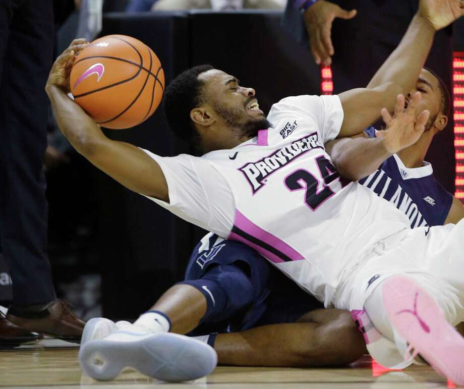 Providence guard Kyron Cartwright (24) grimaces as he falls to the court after winning control of a loose ball against Villanova guard Mikal Bridges, right, during the second half of an NCAA college basketball game Wednesday, Feb. 14, 2018, in Providence, R.I. Providence upset No. 3 Villanova, 76-71. (AP Photo/Stephan Savoia) Photo: Stephan Savoia / Copyright 2018 The Associated Press. All rights reserved.