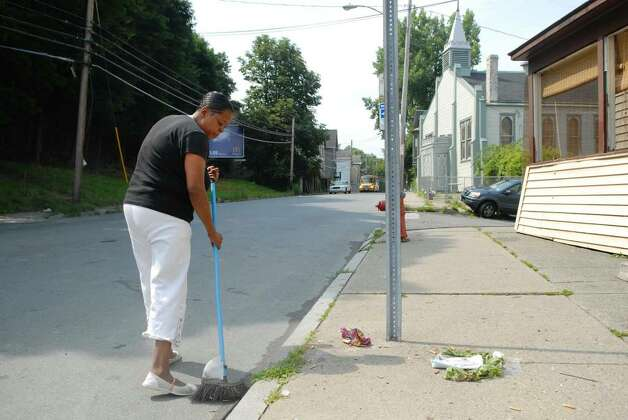 Fourth Street resident Alease Kennedy sweeps up her sidewalk on Wednesday, near where 5-year-old Khayzier Pugh was hit and killed by an unmarked police car. Kennedy says vehicles routinely speed on that section of Fourth Street.  (Paul Buckowski / Times Union) Photo: PAUL BUCKOWSKI