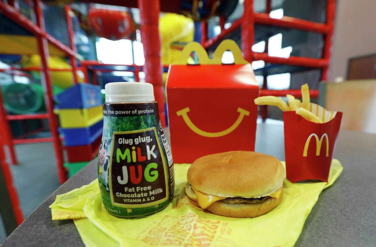 A Happy Meal featuring non-fat chocolate milk and a cheeseburger with fries, are arranged for a photo at a McDonald's restaurant in Brandon, Miss., Wednesday, Feb. 14, 2018. McDonald's will soon banish cheeseburgers and chocolate milk from its Happy Meal menu in an effort to cut down on the calories, sodium, saturated fat and sugar that kids consume at its restaurants. Diners can still ask specifically for cheeseburgers or chocolate milk with the kid's meal, but the fast-food company said that not listing them will reduce how often they're ordered.