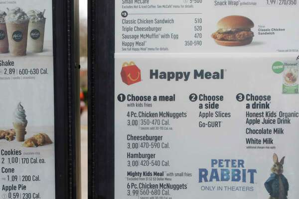 A portion of a drive thru menu panel featuring Happy Meals is seen at a McDonald's Restaurant in Ridgeland, Miss., on Wednesday, Feb. 14, 2018. The company will soon banish cheeseburgers and chocolate milk from its Happy Meal menu in an effort to cut down on the calories, sodium, saturated fat and sugar that kids consume at its restaurants. Diners can still ask specifically for cheeseburgers or chocolate milk with the kid's meal, but the fast-food company said that not listing them will reduce how often they're ordered.