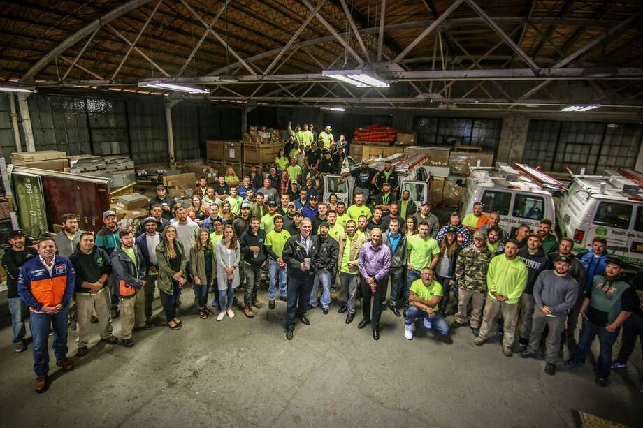 Monolith Solar CEO Mike Hickey, center, in black jacket, poses with employees at one of the company's warehouses.