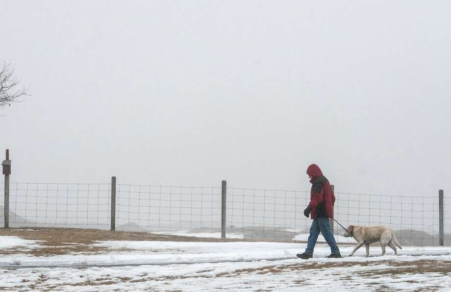 A man and his dog walk through the fog-shrouded Crossings park in Colonie Thursday morning. Photo: Skip Dickstein / Times Union