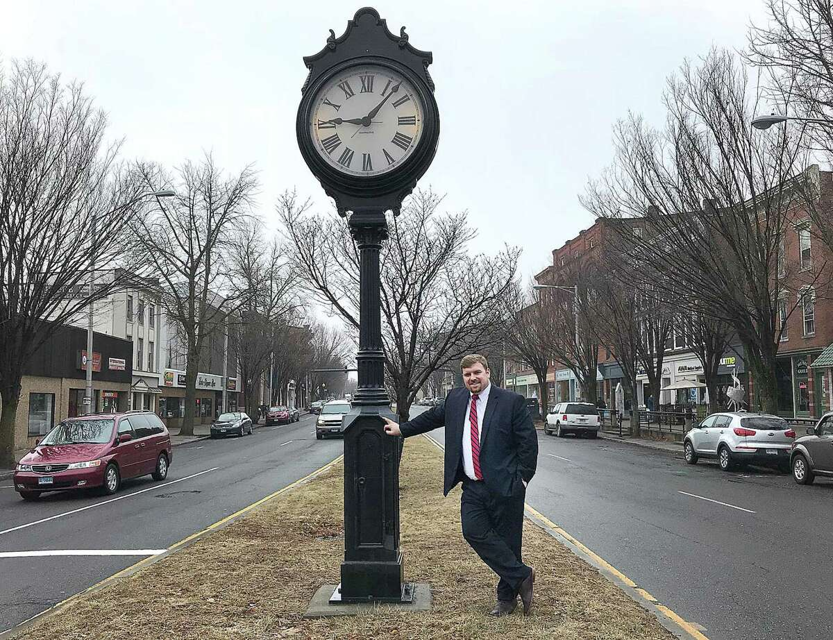 Newly named Greater Danbury Chamber of Commerce President and CEO P.J. Prunty stands by the clock in downtown Danbury, Conn., on Thursday, Feb. 15, 2018.