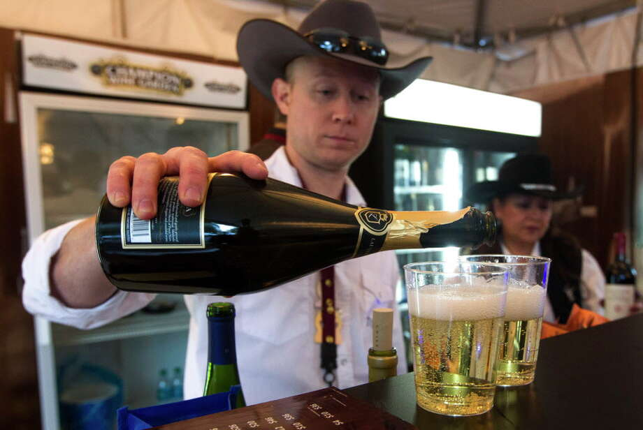 Bartender Sean Humes pours customers a glass of wine at the Champion Wine Garden during the Houston Livestock Show and Rodeo in 2014. This year's Champion Wine Garden returns at the 2018 Rodeo. ( J. Patric Schneider / For the Chronicle ) Photo: J. Patric Schneider, Freelance / © 2014 Houston Chronicle