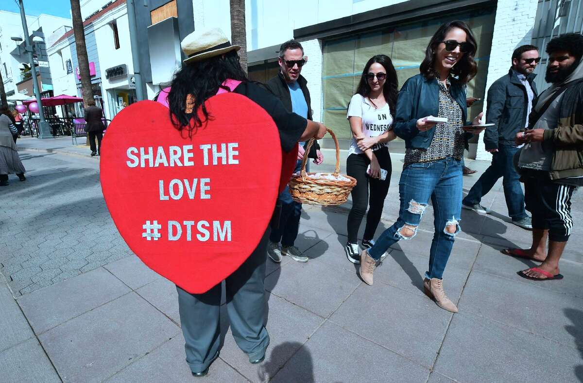DACA youth and members of the California Dream Network hand out candy and flowers celebrating Valentine's Day at the Santa Monica Promenade in Santa Monica, California on February 14, 2018 using the opportunity to ask passersby's to call their senators requesting a vote with love for an immigration bill that protects immigrant youth from arrest, detention and deportation when DACA protections run out on March 5. The