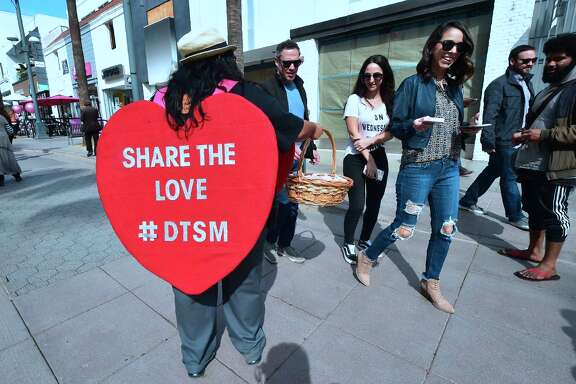 "DACA youth and members of the California Dream Network hand out candy and flowers celebrating Valentine's Day at the Santa Monica Promenade in Santa Monica, California on February 14, 2018 using the opportunity to ask passersby's to call their senators requesting a vote with love for an immigration bill that protects immigrant youth from arrest, detention and deportation when DACA protections run out on March 5. The ""Vote for LOVE"" outreach effort is a direct message to both Congress and voters to think about the most basic of human sentiments -- love -- when engaging in a debate about a DACA-fix deal this week.      / AFP PHOTO / Frederic J. BROWNFREDERIC J. BROWN/AFP/Getty Images"