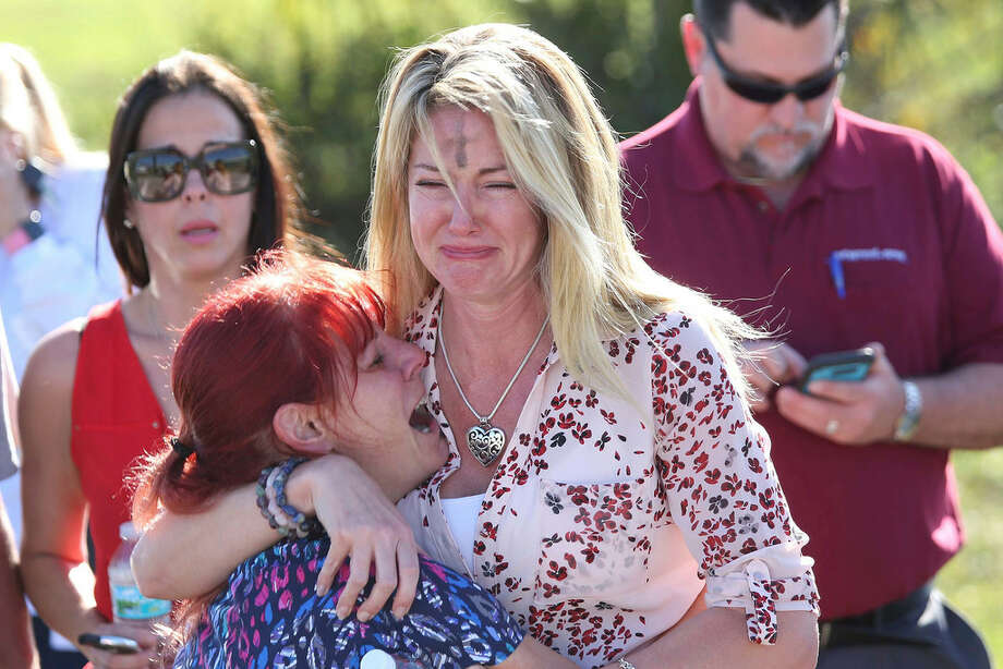 Wearing ashes, a parent waits after the shooting at Marjory Stoneman Douglas High School in Parkland, Fla., on Wednesday, Feb. 14, 2018.