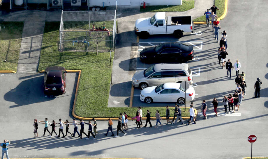 Students are evacuated by police from Marjorie Stoneman Douglas High School in Parkland, Fla., on Wednesday, Feb. 14, 2018.