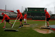 Lamar baseball student assistants roll water off the turf during a weather delay in the opening game of the Cardinal Classic. The Cardinals' season opener against Wisconsin-Milwaukee was postponed to 10 a.m. today.  Photo taken Friday 2/17/17 Ryan Pelham/The Enterprise