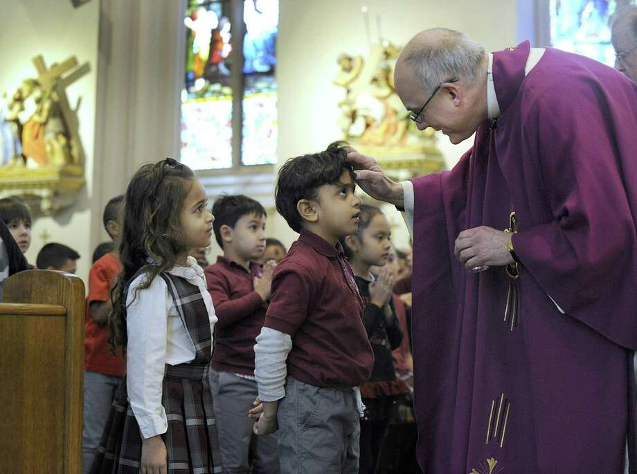 Andressa Porto waits her turn as Abraham Duque receives ashes from Father Gregg Mecca, pastor of St. Peter Church in Danbury on Ash Wednesday. The children are students at St. Peter School. Photo: Carol Kaliff / Hearst Connecticut Media / The News-Times