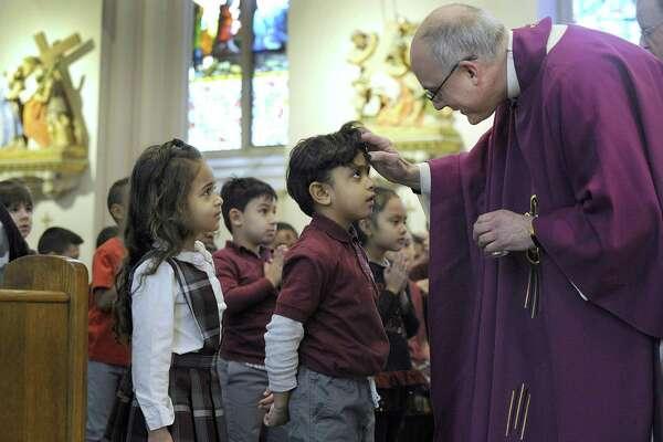 Andressa Porto waits her turn as Abraham Duque receives ashes from Father Gregg Mecca, pastor of St. Peter Church in Danbury on Ash Wednesday. The children are students at St. Peter School.