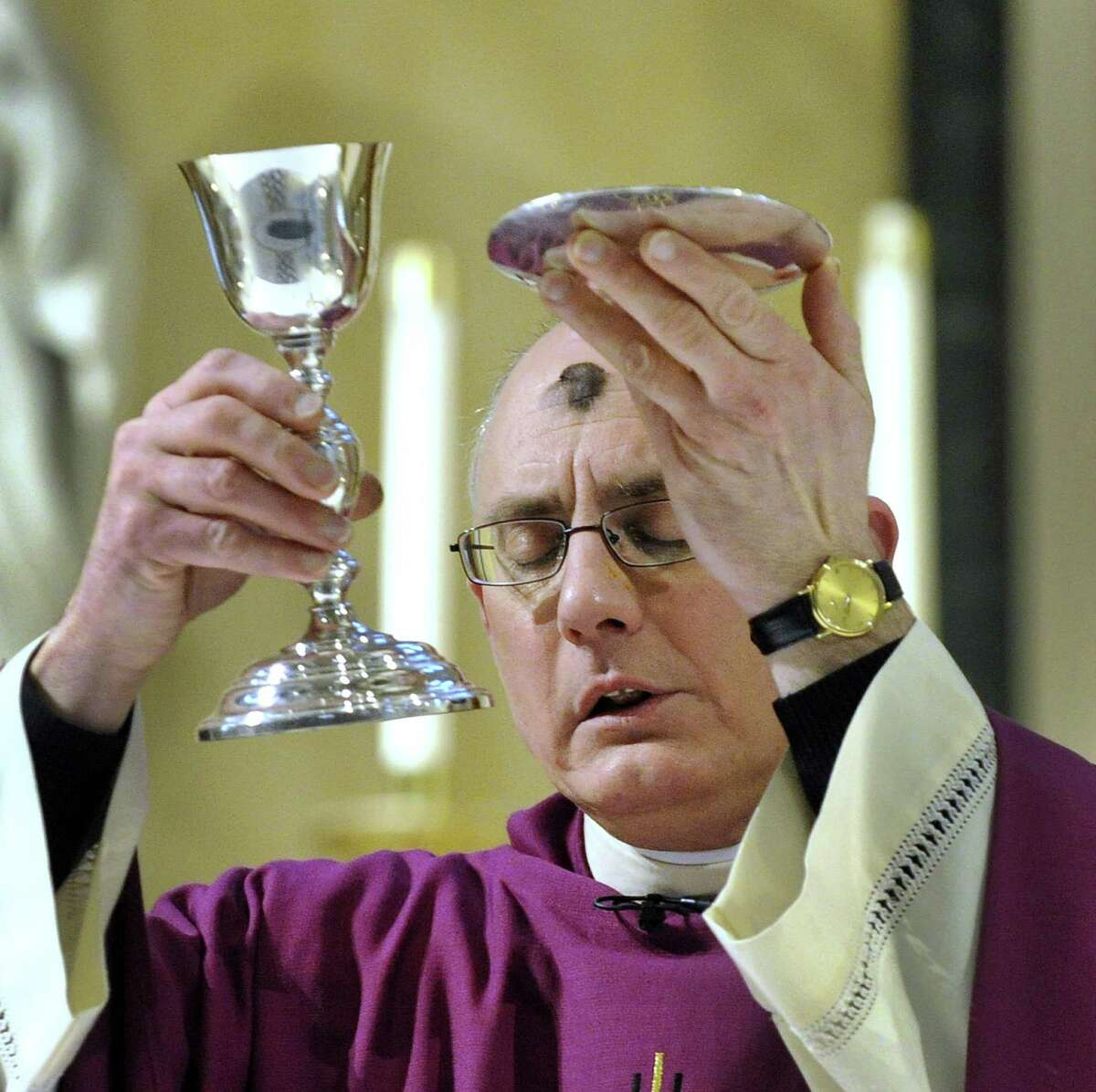 Father Gregg Mecca, pastor of St. Peter Church in Danbury, blesses the communion elements at a morning Ash Wednesday Mass, Feb. 14, 2018.