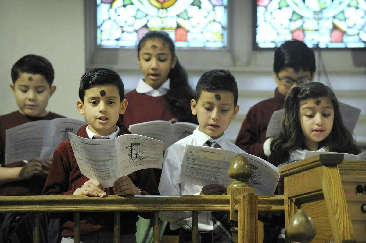 The St. Peter School Choir, including in the front row from left, fourth- graders Jaime Granillo, Jonathan Galindo and Lida Jimenez, sing during an Ash Wednesday Mass at St. Peter Church in Danbury.
