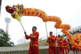 "Members of the San Antonio Chinese Dragon Dance Team join in a mini-parade as the Institute of Texan Cultures hosts the 2017 Asian Festival on Saturday, Feb. 4, 2017. In conjunction with the Asian New Year, ITC marked a milestone of 30 years hosting the festival. Guests were treated to various types of Asian foods, cultural performances and even ""Mah Jong"" - a game similar to the card game, Bridge, - that is played on tiles on felt table. Attendance was steady despite cooler temperatures and a light mist. UTSA President Ricardo Romo helped kick off the event with the lighting of a long strand of firecrackers before leading Chinese lion and dragon dancers with a mini-parade to start off the celebration."