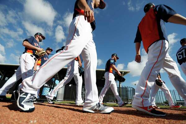Houston Astros pitchers walk out of a group meeting as they began their workouts for the day during spring training at The Ballpark of the Palm Beaches, Thursday, Feb. 15, 2018, in West Palm Beach .