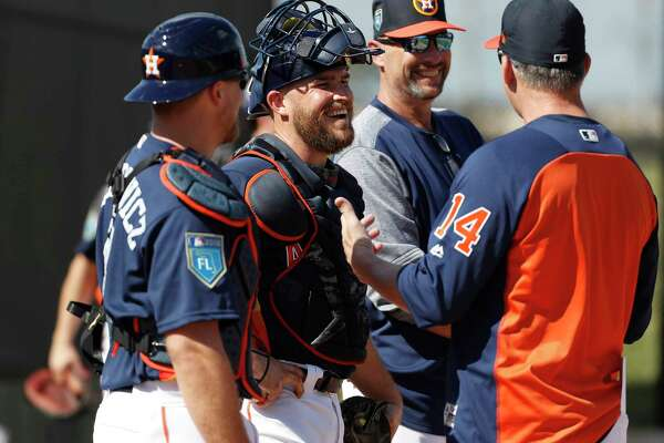 Houston Astros catchers Max Stassi (12) and Tim Federowicz (44) laugh with manager A.J. Hinch (14) as the pitchers and catchers worked out during spring training at The Ballpark of the Palm Beaches, Thursday, Feb. 15, 2018, in West Palm Beach .