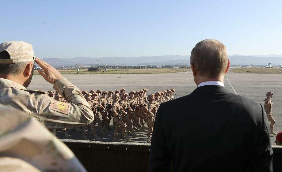 Russian President Vladimir Putin (right) watches troops last year at the Hemeimeem air base in Syria. Photo: Mikhail Klimentyev, Associated Press