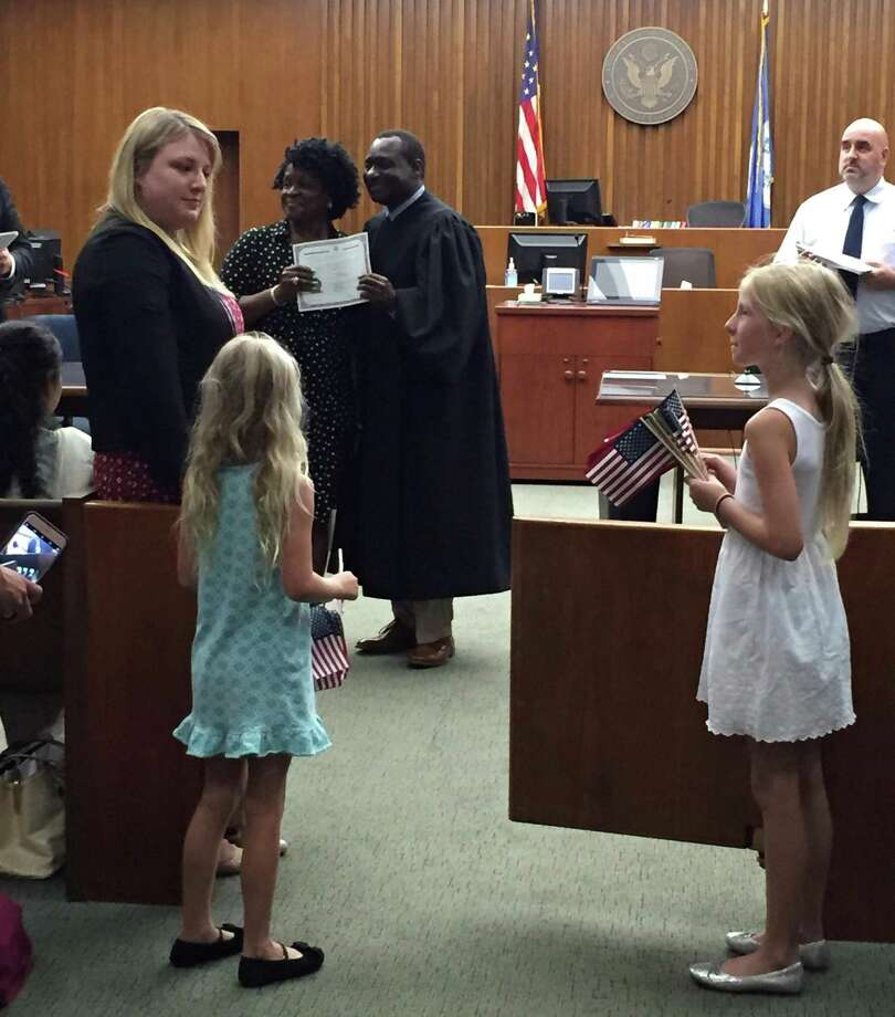 Sheila Ward's daughters handed American flags at a naturalization ceremony in the Bridgeport federal courthouse, something the League of Women Voters regularly does to welcome new citizens. Photo: Contributed Photo