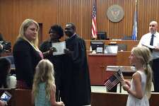 Sheila Ward's daughters handed American flags at a naturalization ceremony in the Bridgeport federal courthouse, something the League of Women Voters regularly does to welcome new citizens.