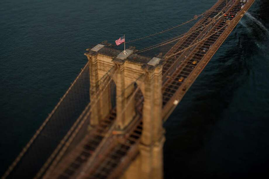 ad7a38f6b05 An American flag flies on top of the Brooklyn Bridge in this aerial  photograph taken with