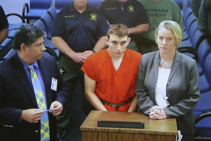 A video monitor shows school shooting suspect Nikolas Cruz, center, making an appearance before Judge Kim Theresa Mollica in Broward County Court, Thursday, Feb. 15, 2018, in Fort Lauderdale, Fla.  Cruz is accused of opening fire Wednesday at Marjory Stoneman Douglas High School in Parkland, Fla., killing more than a dozen people and injuring several.