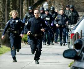 Blacksburg police officers run from Norris Hall on the Virginia Tech campus in Blacksburg, Va., Monday, April 16, 2007. Multiple shootings occurred at the engineering building on Monday. A gunman opened fire in a Virginia Tech dorm and then, two hours later, in a classroom across campus Monday, killing at least 30 people. (AP Photo/The Roanoke Times, Matt Gentry)  **MANDATORY CREDIT **