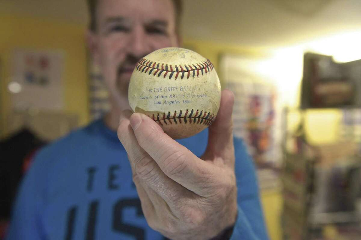 Jim Keller, of New Fairfield, has been collecting Olympic memorabilia since 1972. Keller holds a baseball that was hit out of the park for a home run in the 1984 Summer Games in Los Angeles, Califirnia. keller was a volunteer at the games and walking by the outside of the baseball stadium during a team USA game when the ball fell right near him. Wednesday, February 14, 2018, in New Fairfield, Conn.