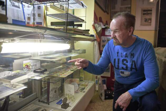 Jim Keller, of New Fairfield, has been collecting Olympic memorabilia since 1972. Keller points out a coin from the 1912 games in Stockholm , Sweeden, that was a gift from his daughter. Wednesday, February 14, 2018, in New Fairfield, Conn.